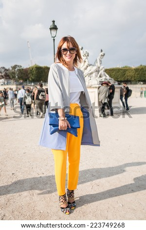 PARIS - SEPTEMBER 30, 2014: Stylish european woman with yellow trousers in the Tuileries Garden. Paris Fashion Week: Ready to Wear is held from September 23 to October 1. - stock photo