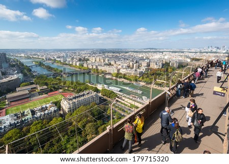PARIS - SEPTEMBER 20, 2013: Tourists are on the observation deck of the Eiffel Tower in Paris. The Eiffel tower is one of the major tourist attractions of France.