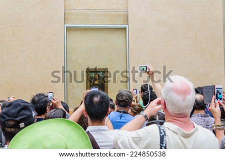 PARIS - SEPTEMBER, 17: Visitors take photo of Leonardo DaVinci's Mona Lisa at the Louvre Museum on September, 2014 in Paris, France. Gioconda is one of the world's most famous pictures in the world.  - stock photo