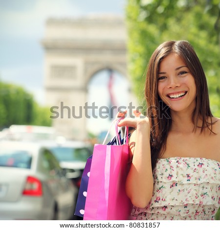 Paris shopping woman tourist on Champs-e?lysees with Arc de Triomphe in the background carrying shopping bags outside in Paris. Pretty Asian Caucasian female model.