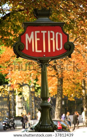 Parisian metro sign with autumn trees in the background - stock photo