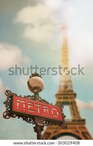 Parisian metro sign with blurred Eiffel Tower in the background. Lightly textured.