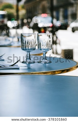 Parisian street restaurant cafe with defocused background - round table is set in the most romatic city - Paris, France - stock photo