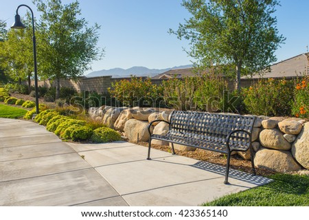 Park bench along an empty sidewalk in quiet California residential neighborhood. - stock photo