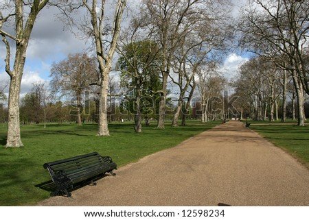 Park bench and path in Hyde Park, London, England - stock photo