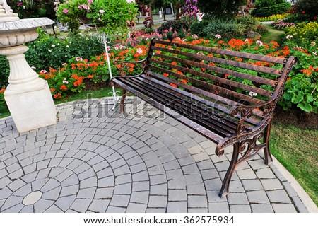 Park Bench in a flower garden. - stock photo