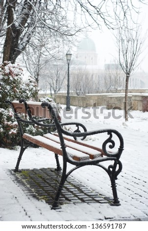 park bench on a winter alley at snowfall