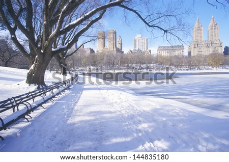 Park benches with snow in Central Park on the shore of the Reservoir, Manhattan, New York City, NY - stock photo