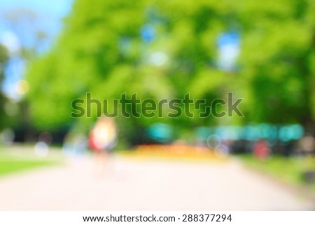 Park full of people in summer, blurred background - stock photo