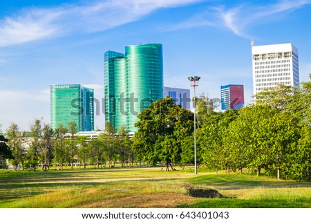 Park green grass building background under blue sky with downtown skyline