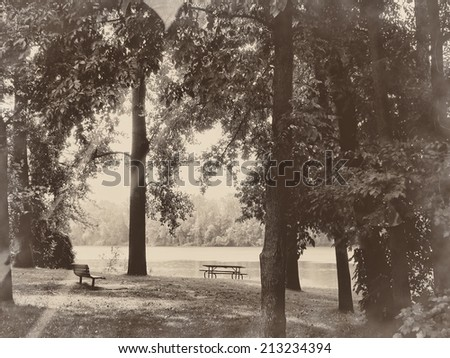 Park near the river - picnic table, trees and river, relaxing nature in sepia retro vintage  - stock photo