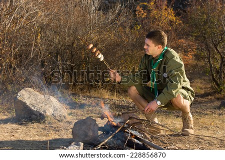 Park ranger or scout cooking sausages over a small open fire in a campsite checking them to see if they are cooked