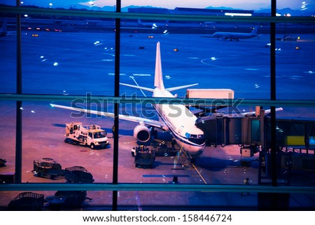 Parked aircraft on beijing airport through the gate window - stock photo