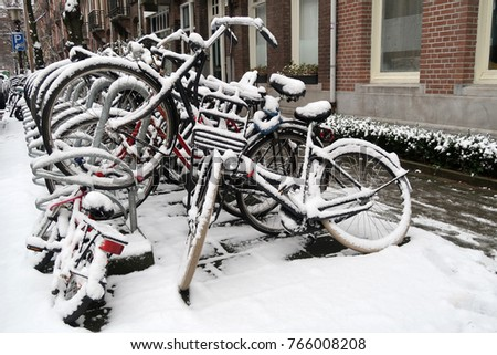 Parked bicycles covered with snow