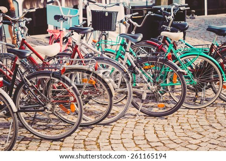 Parked Bicycles On Sidewalk. Bike Bicycle Parking In Big City. Toned Instant Filtered Photo - stock photo