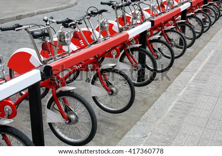 parked city bicycles on sidewalk in the city, bike share station  - stock photo