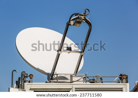 Parked satellite truck transmits breaking news events to orbiting satellites for broadcast around the world - stock photo