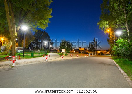 Parking at the Vistula river with night view for old town of Torun, Poland - stock photo