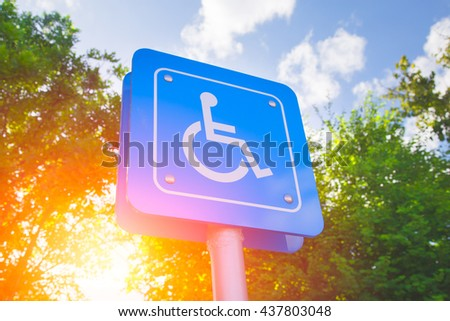 Parking for disability persons sign with green and sun light background. - stock photo