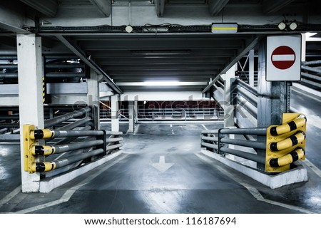 Parking garage in basement, underground interior, stop sign entrance. Neon light in bright industrial building.