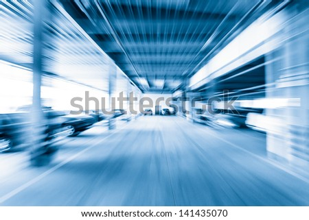 Parking garage, interior with a few parked cars.Motion blur - stock photo