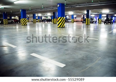 Parking garage of shopping center, underground interior. Neon light in bright industrial building. - stock photo