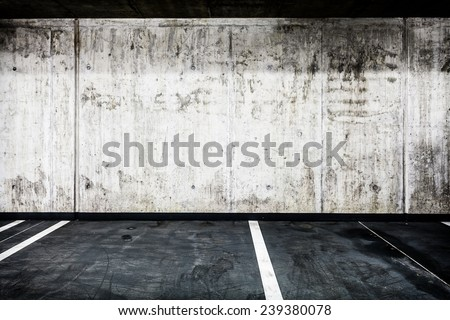 Parking garage underground interior background or texture. Concrete grunge wall and asphalt road, industrial retro vintage interior.