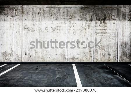 Parking garage underground interior background or texture. Concrete grunge wall and asphalt road, industrial retro vintage interior. - stock photo