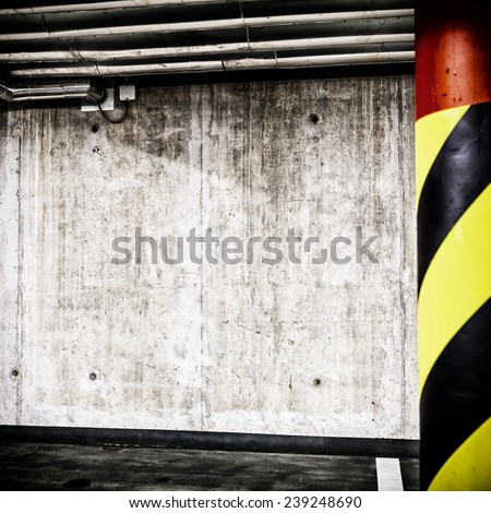 Parking garage underground interior background or texture. Concrete grunge wall and column with warning sign, industrial retro vintage interior. - stock photo