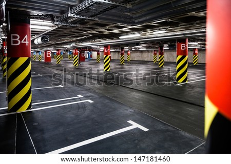 Parking garage underground interior, neon lights in dark industrial building, modern public construction