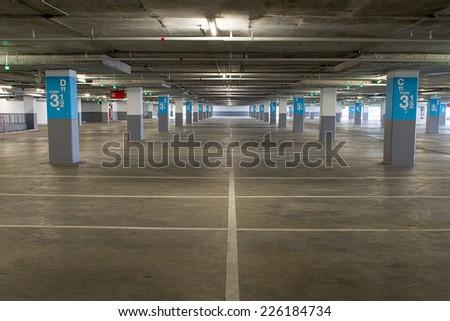 Parking garage underground interior, neon lights in dark industrial building, modern public construction - stock photo