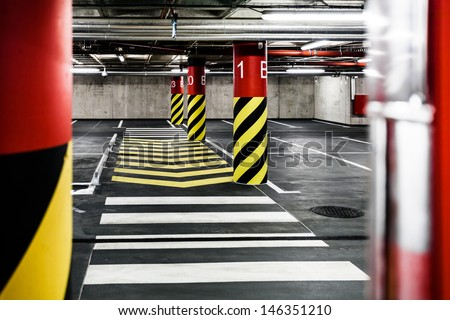 Parking garage underground interior, pedestrian crossing, neon lights in dark industrial building, modern public construction - stock photo