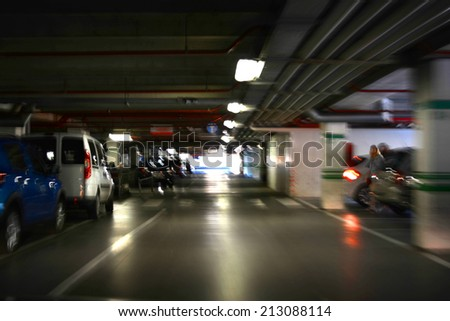 Parking garage, underground interior with a few parked cars. Intentional motion blur - stock photo