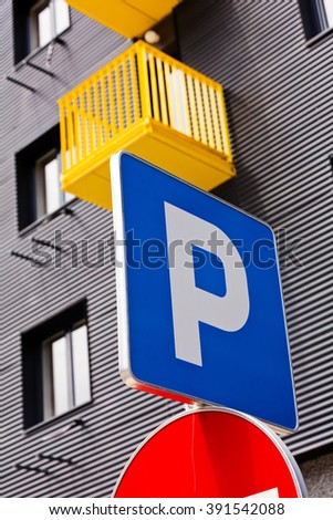 Parking sign with building with yellow balcony in background - stock photo
