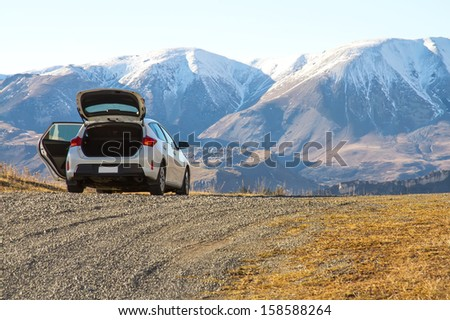Parking white car in front of mountain - stock photo