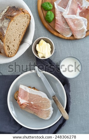 Parma ham on rustic sourdough bread with butter and milk - stock photo