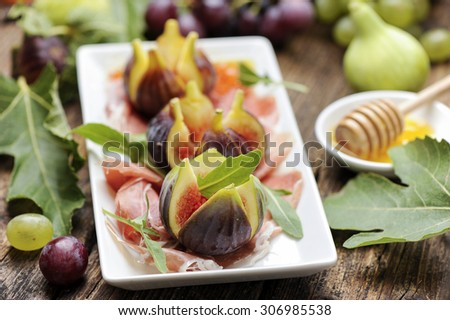 Parma Ham  with figs on a wooden table - stock photo