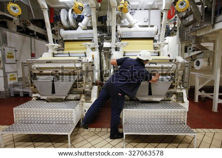 PARMA, ITALY - 3 OCTOBER 2012: An employee checking a machine as freshly-shaped pasta falls into feeders on the production line inside a pasta factory.