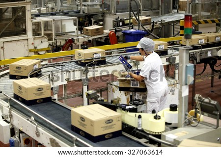 PARMA, ITALY - 3 OCTOBER 2012: An employee checking boxes of packaged pasta for quality control as they travel along the production line inside a pasta factory.