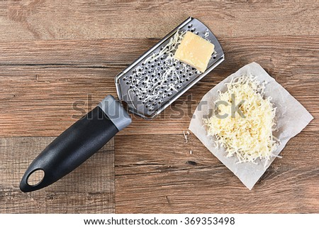 Parmesan Cheese and grater on a wood kitchen table. Some grated cheese is on a piece of parchment paper next to the grater. High angle view in horizontal format. - stock photo