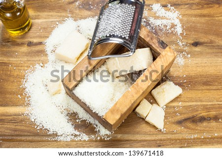 Parmesan cheese. Grated Parmesan cheese. Olive Wood Parmesan Cheese Grater. Viewed from above - stock photo