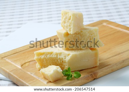 Parmesan cheese pieces on a cutting board - stock photo
