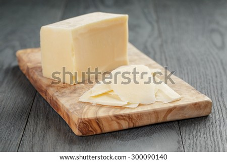 parmesan cheese sliced on olive board, over oak table - stock photo