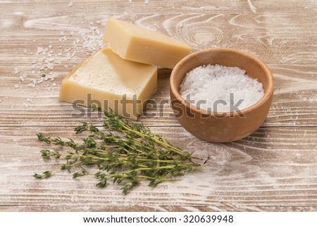Parmesan cheese with sea salt and thyme on whitewashed wood surface - stock photo