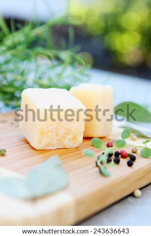 Parmesan cheese with spices and herbs on a wooden board