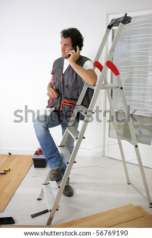 Parquet layer on phone leaning on a ladder - stock photo