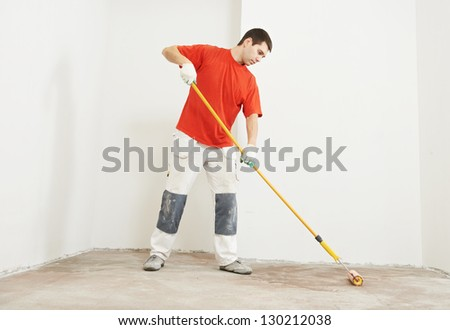 Parquet worker with paint roller making floor prime coating  at home repair renovation work - stock photo