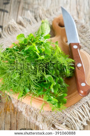 Parsley and dill on a wooden table.