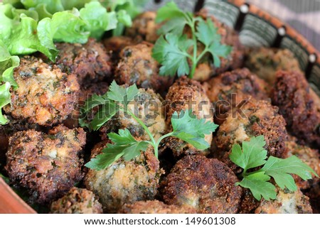 Parsley balls with white pepper and salad - stock photo
