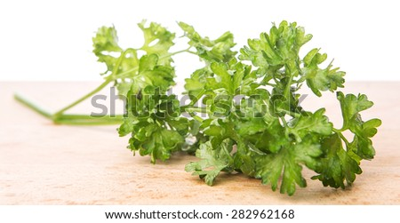 Parsley herbs leaves on wooden surface.